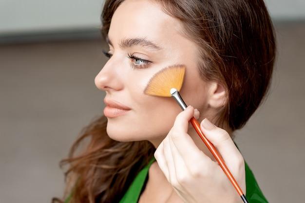 La truccatrice applica una base tonale cosmetica secca sul viso usando il pennello per il trucco. perfetto trucco naturale con l'applicazione del fard.