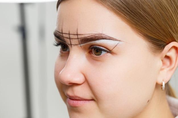 Il truccatore applica la tinta per sopracciglia per il trucco permanente di una giovane ragazza. trucco professionale e cura cosmetica del viso