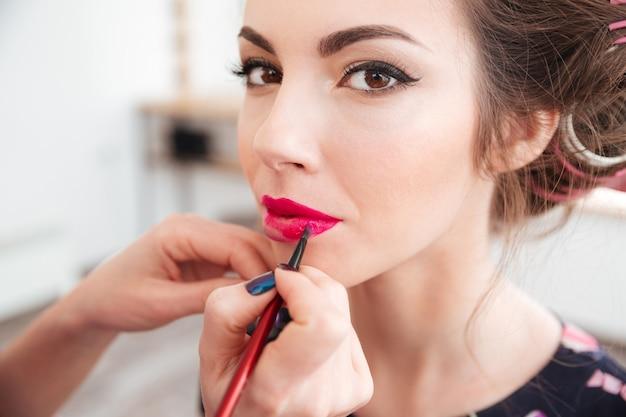Artista di trucco che applica rossetto rosa brillante alle labbra della giovane donna in bigodini