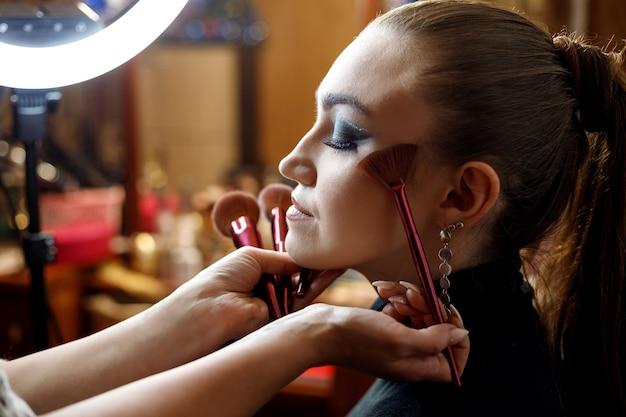 Un truccatore fa il trucco per una giovane bella ragazza in un salone di bellezza.