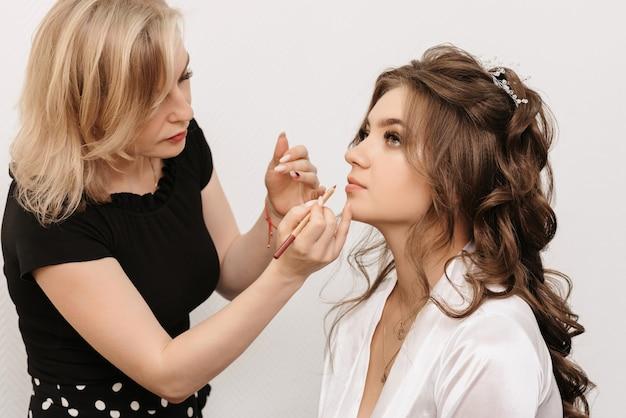 Il truccatore dipinge le labbra di una giovane ragazza attraente con una matita per le labbra in un salone di bellezza