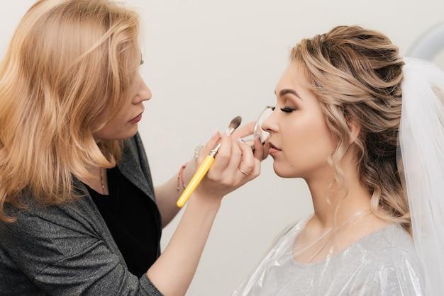 La truccatrice dipinge le labbra di una giovane ragazza con il rossetto in un salone di bellezza