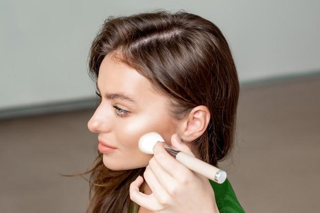 Il truccatore utilizza il pennello per il trucco applica una base tonale cosmetica secca sul viso della donna.