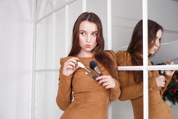 Truccatrice con lunghi capelli scuri che tiene un pennello da cipria, espressione altezzosa, riflesso nello specchio