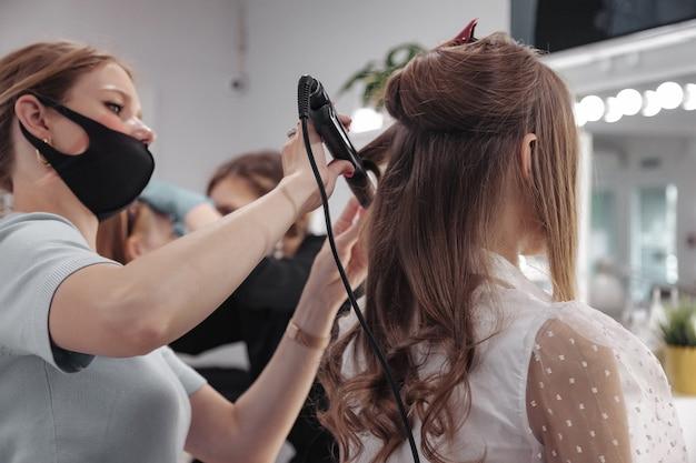 I truccatori compongono le giovani donne nel salone di bellezza. servizio clienti nella stanza interna per creare un'immagine straordinaria. procedura guidata per la creazione del trucco da lavoro. concetto di stile e misura della soddisfazione. copia spazio