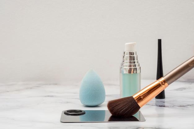 Pennello trucco con tavolozza da applicare e cosmetici su base marmo con composizione estetica