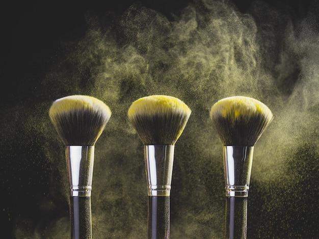 Pennello da trucco con esplosione di polvere gialla su sfondo nero
