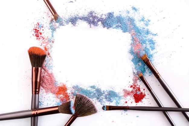 I pennelli per il trucco incorniciano con blush e ombretto nei toni del rosa, del blu e del corallo