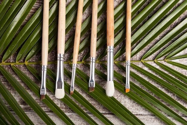 Pennelli trucco su foglie su fondo in legno