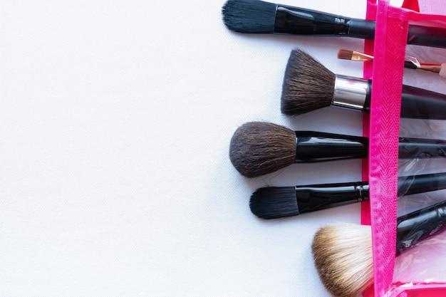 Pennelli per il trucco in un sacchetto di cosmetici rosa su sfondo bianco