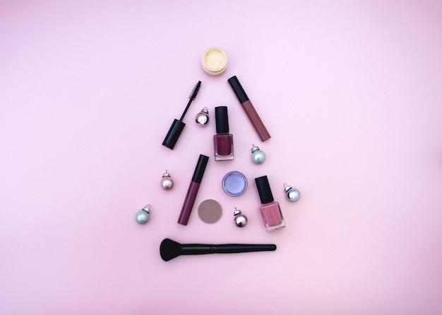 Trucco prodotti cosmetici ombrettoslipstick mascara albero di natale piatto su sfondo rosa