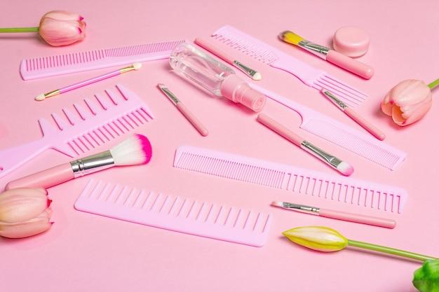 Set di cosmetici per il trucco e pettini per capelli sul rosa.