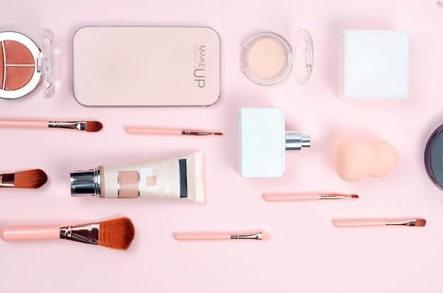 Trucco cosmetico decorativo, pennelli, strumenti e accessori su sfondo rosa pastello.