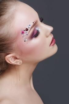 Trucco sopra le sopracciglia delle donne molti strass di diverse forme, bella cura della pelle liscia del viso. trucco di bellezza sul primo piano del fronte della donna