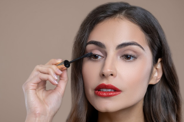 Trucco, occhi. focalizzata donna dai capelli scuri dagli occhi marroni con labbra rosse che applica mascara tenendo l'applicatore vicino al suo occhio