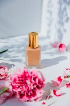 Trucco fondotinta in crema con fiori di dianthus sulla parete bianca