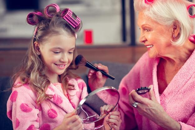 Trucco per ragazza. amorevole nonna raggiante che fa il trucco per la sua bambina carina mentre indossa bigodini