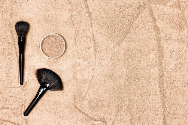 Polvere per il trucco con pennelli per il trucco texture sfusa di cipria copia spazio sfondo di cosmetici