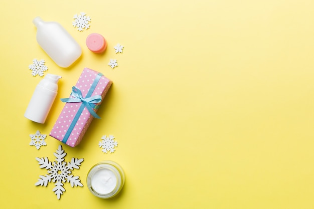 Prodotti per il trucco e decorazioni natalizie su sfondo colorato. vista dall'alto concetto di bellezza del nuovo anno con spazio di copia