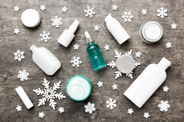 Prodotti per il trucco e decorazioni natalizie su sfondo colorato. vista dall'alto concetto di bellezza del nuovo anno.