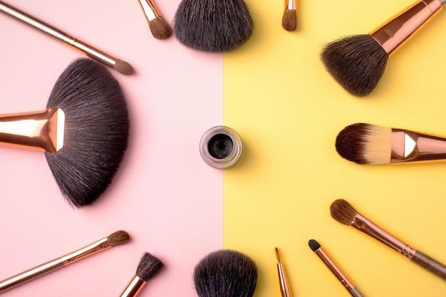 Prodotti per il trucco e pennelli cosmetici con eyeliner su giallo e rosa, laici piatta.