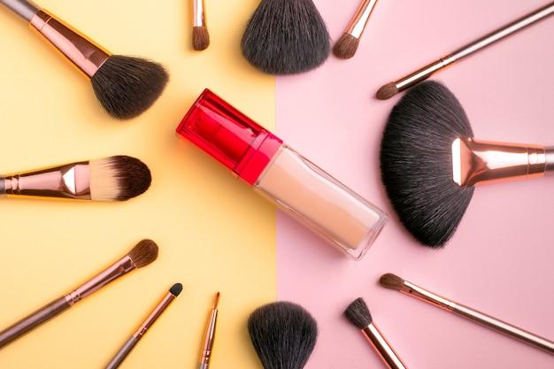 Prodotti per il trucco e pennelli cosmetici con fondamento su sfondo multicolore, laici piatta. concetto di blogging di moda e bellezza. vista dall'alto
