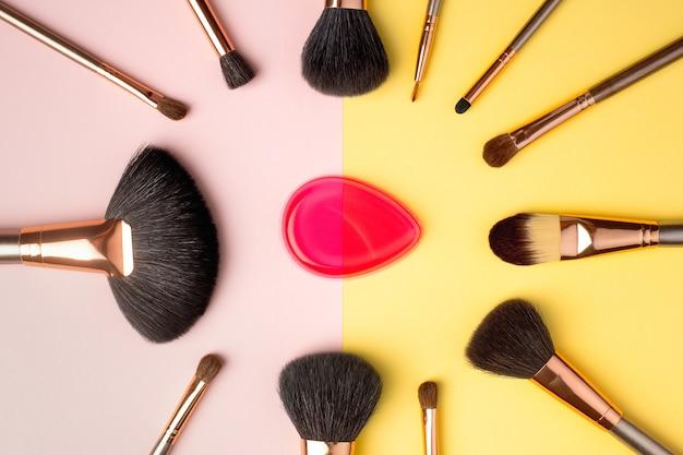 Prodotti per il trucco e pennelli cosmetici con spugna, distesi. concetto di blog di moda e bellezza. vista dall'alto