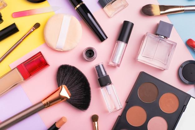 Prodotti per il trucco e cosmetici su sfondo multicolore, piatto laici. concetto di blog di moda e bellezza. vista dall'alto