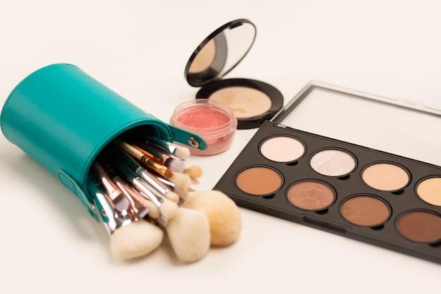 Set trucco: kit pennelli in astuccio, palette di evidenziatori e bronzer e fard su fondo grigio