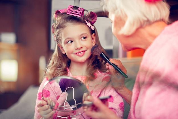 Trucco con la nonna. ragazza carina dagli occhi scuri che si sente eccitata mentre si trucca con la nonna per la prima volta