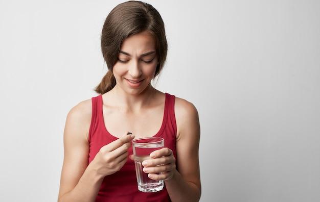 La donna di trucco in maglietta rossa tiene i problemi di salute della medicina della pillola dell'acqua del bicchiere.