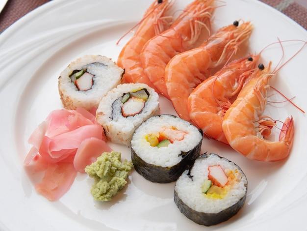 I rotoli di maki (cibo giapponese) serviti con gamberi bolliti sono pronti da mangiare su un piatto bianco.