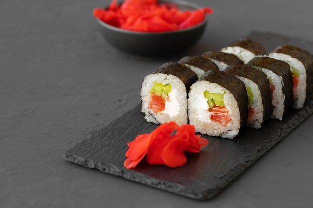 Maki sushi roll servito su lastra di pietra su sfondo grigio si chiuda