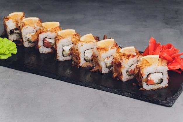 Maki sushi rolls con salmone su pietra nera su sfondo scuro. con zenzero e wasabi. menu di sushi. cibo giapponese. primo piano di delizioso cibo giapponese con rotolo di sushi. foto orizzontale.