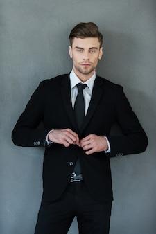 Fare affari con un bell'aspetto. bel giovane uomo d'affari che si aggiusta la giacca e guarda la telecamera Foto Premium