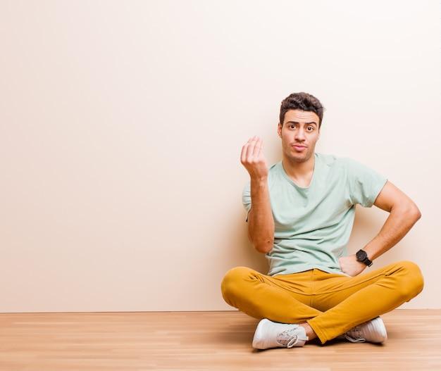 Facendo un gesto di capice o denaro, dicendoti di pagare i tuoi debiti!