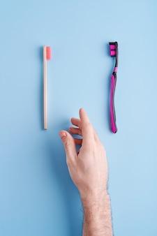 Scegliere tra spazzolino da denti in plastica e spazzolino da denti in bambù ecologico. tendenze ecologiche in tutto il mondo.