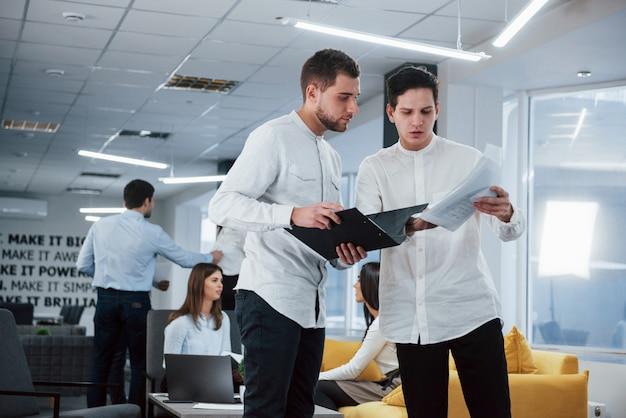 Correzioni nel rapporto. due impiegati in abiti classici, parlando di fronte a dipendenti
