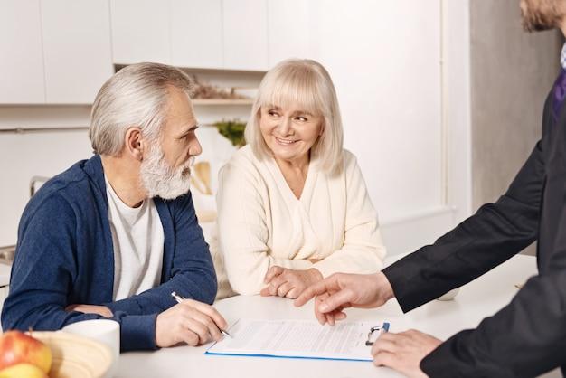 Prendere una decisione cruciale. ottimista allegra sincera coppia senior seduti a casa e incontrando l'agente immobiliare durante la firma dell'accordo