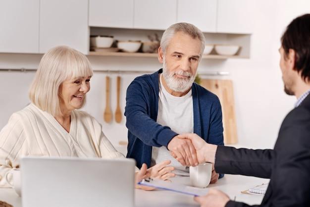 Fare affari. sorridente coppia di anziani coinvolti seduti a casa e la conclusione di un accordo con l'agente immobiliare mentre esprime positività e stringe la mano