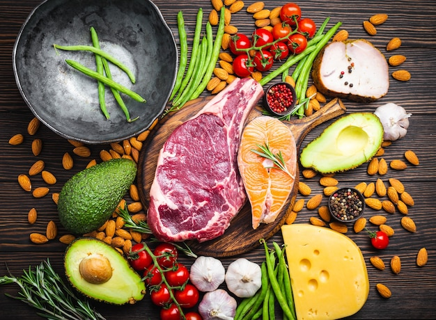 Preparare la cena con ingredienti a basso contenuto di carboidrati per un'alimentazione sana e perdita di peso, vista dall'alto. alimenti cheto: carne, pesce, avocado, formaggio, verdure, noci. dieta chetogenica, alimentazione pulita biologica