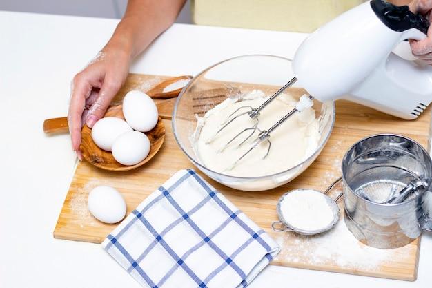 Fare impasti per pane o prodotti da forno fatti in casa. ingredienti in tavola. le mani femminili tengono un mixer per mescolare l'impasto