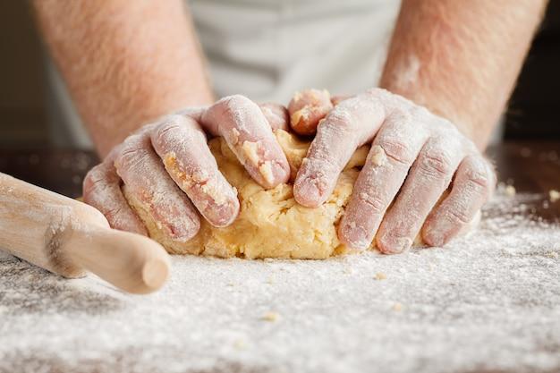 Produrre pasta dalle mani degli uomini sul fondo di legno della tavola