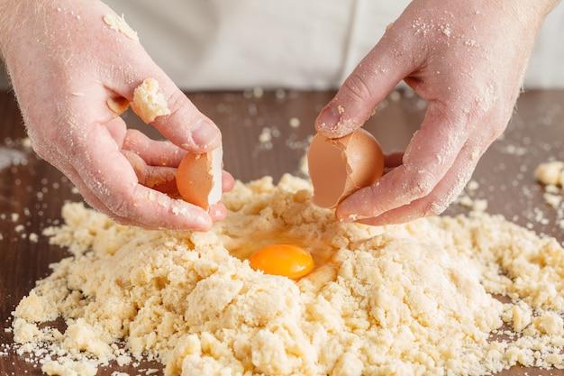 Produrre la pasta dalle mani degli uomini sul fondo di legno della tavola