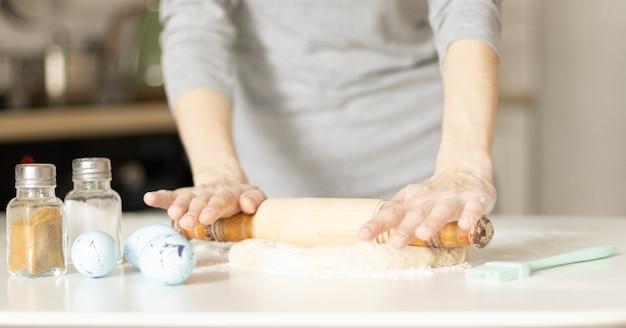 Fare i biscotti di pasqua, mani femminili con la pasta