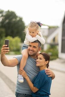 Fare selfie di famiglia. bel marito amorevole che prende smartphone mentre fa selfie in famiglia