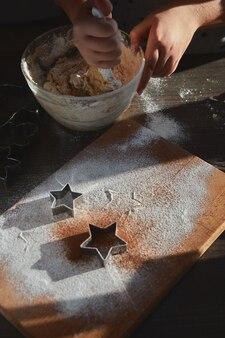 Preparare l'impasto per biscotti allo zenzero. le mani di una giovane donna si mescolano in una lastra di vetro per cuocere la pasta degli uomini di pan di zenzero. il concetto di una festa in casa, una cena in famiglia.