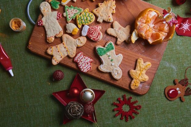 Fare l'uomo di pan di zenzero, pasta per biscotti. il concetto di una festa in casa, una cena in famiglia. concetto di tradizioni di capodanno e processo di cottura. biscotti sul tavolo verde in legno.