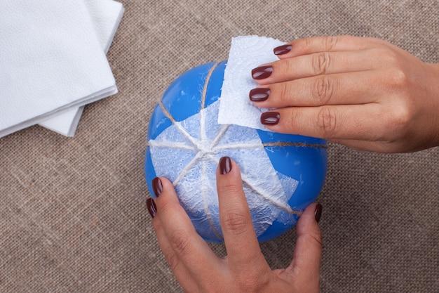Realizzare una zucca di cartapesta fatta in casa da un palloncino e tovaglioli, decorazioni per la celebrazione di halloween.