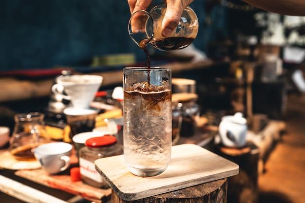 Preparando il caffè ghiacciato, le mani stanno versando il caffè in un bicchiere di acqua fredda.